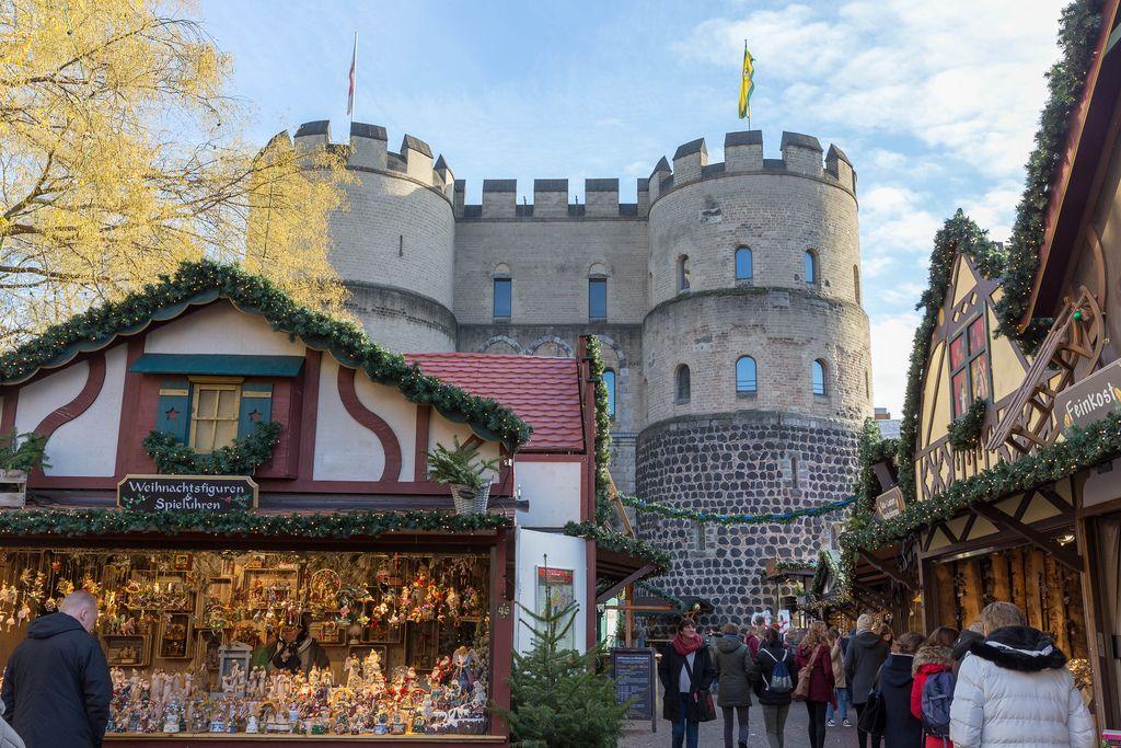 Passanten schlendern durch Weihnachtsmarkt vor alter Kölner Stadtmauer am Kölner Rudolfplatz