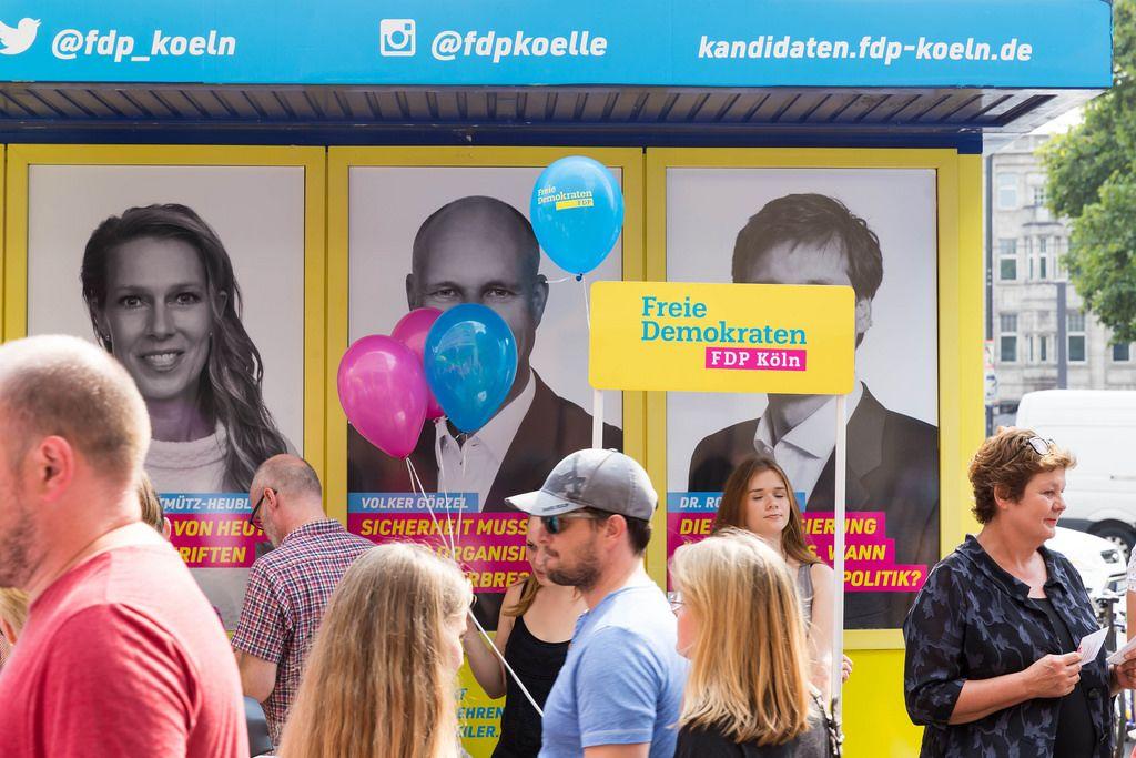 Passanten und ein Promotionstand der FDP im Hintergrund