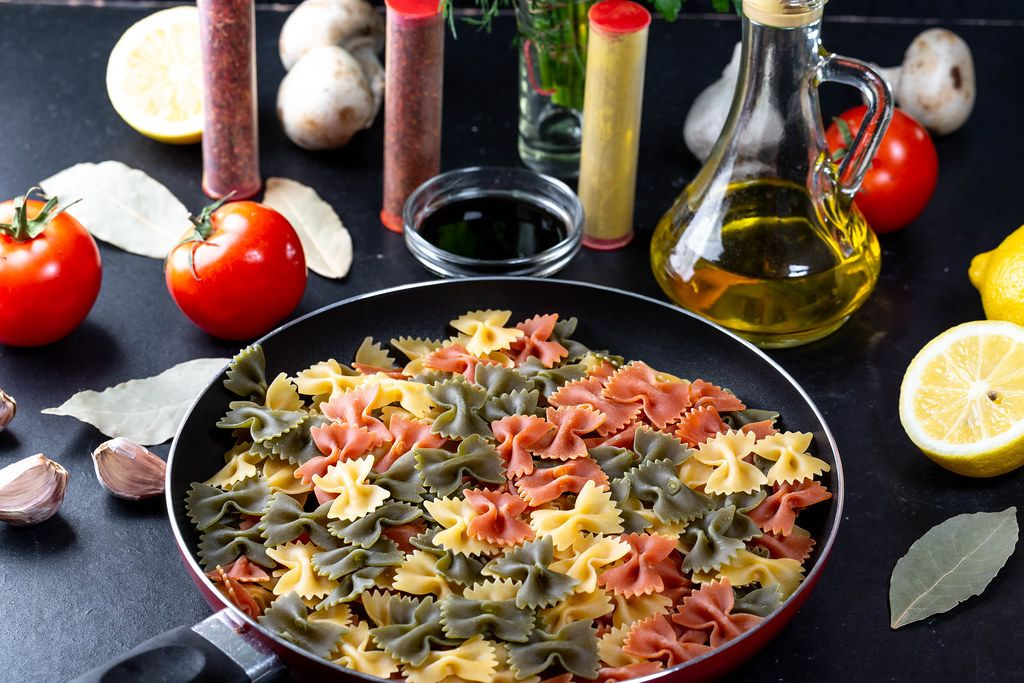 Pasta-bows with spices and fresh herbs on a black table. The concept of cooking