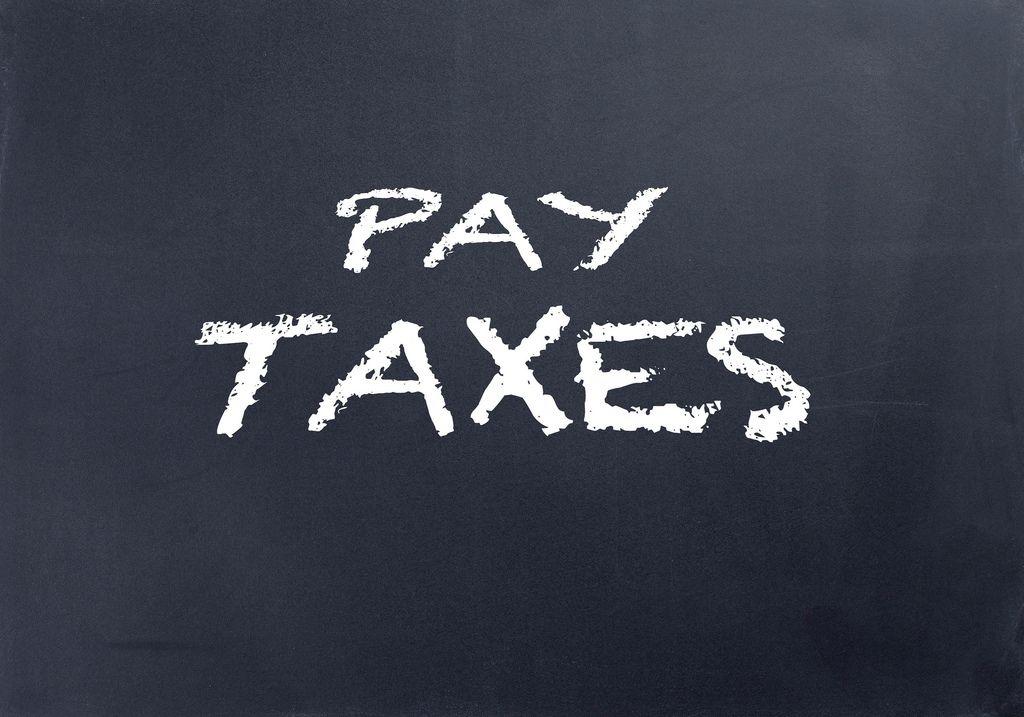 Pay taxes text on blackboard