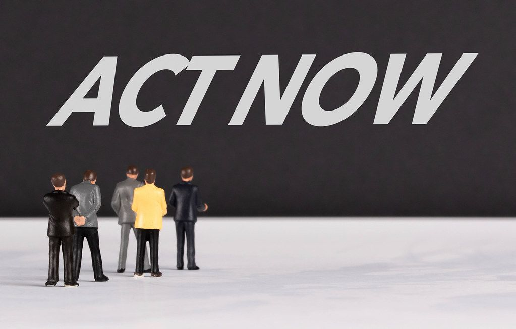 People standing in front of Act Now text