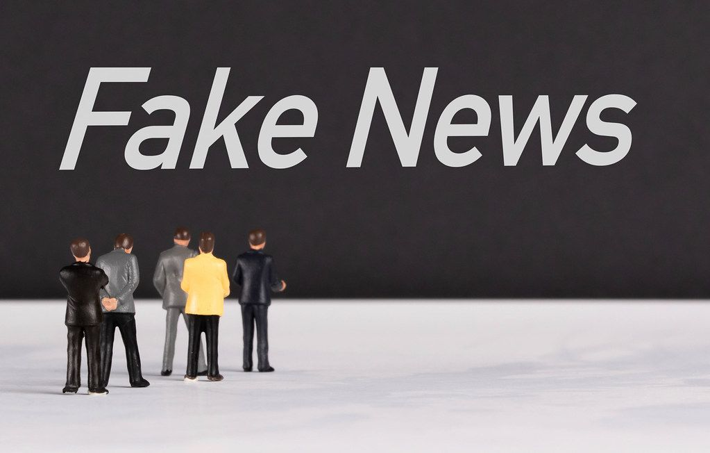 People standing in front of Fake News text