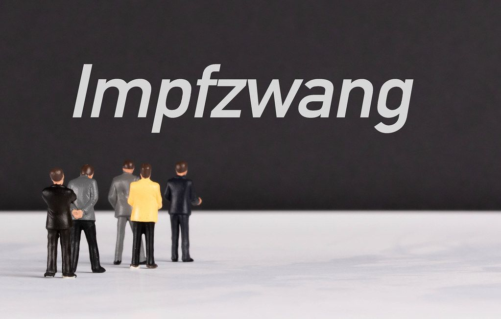 People standing in front of Impfzwang text
