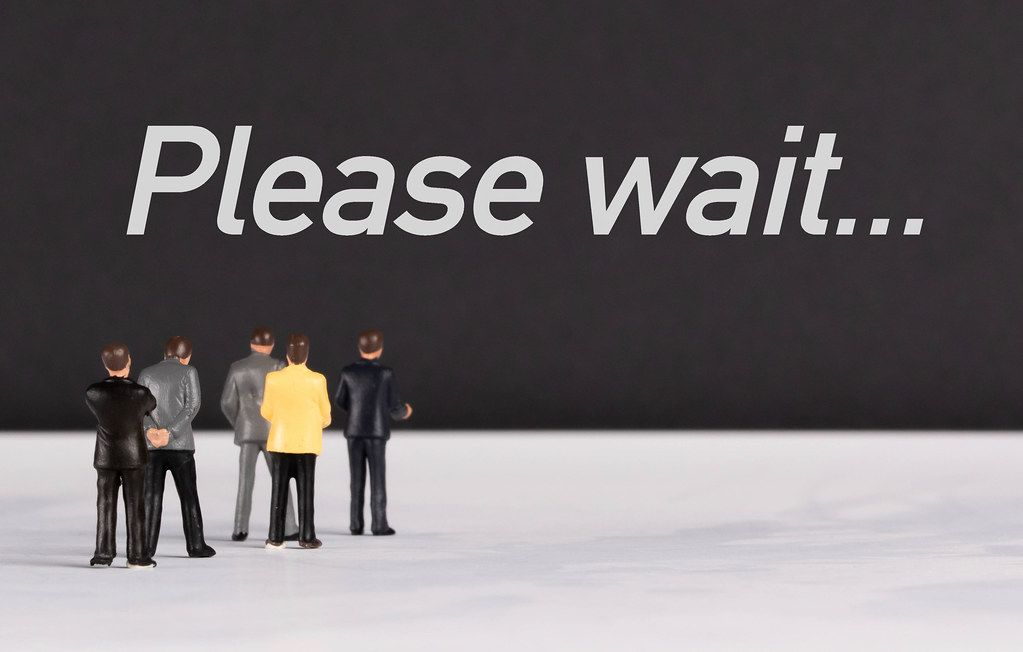 People standing in front of Please Wait text