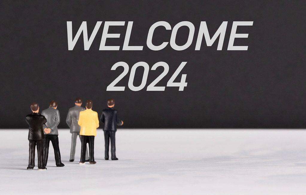 People standing in front of Welcome 2024 text