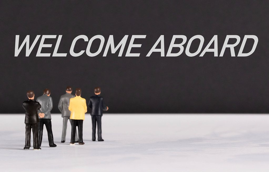 People standing in front of Welcome Aboard text