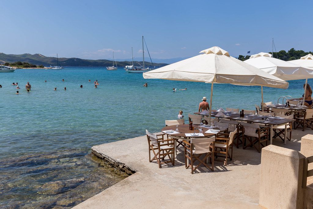 People swimming in the blue sea at Hinitsa Beach, next to restaurant tables under parasols, on a greek island