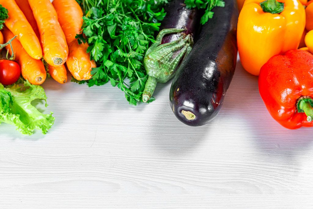Pepper, eggplant, parsley and carrot on white wooden background (Flip 2019)