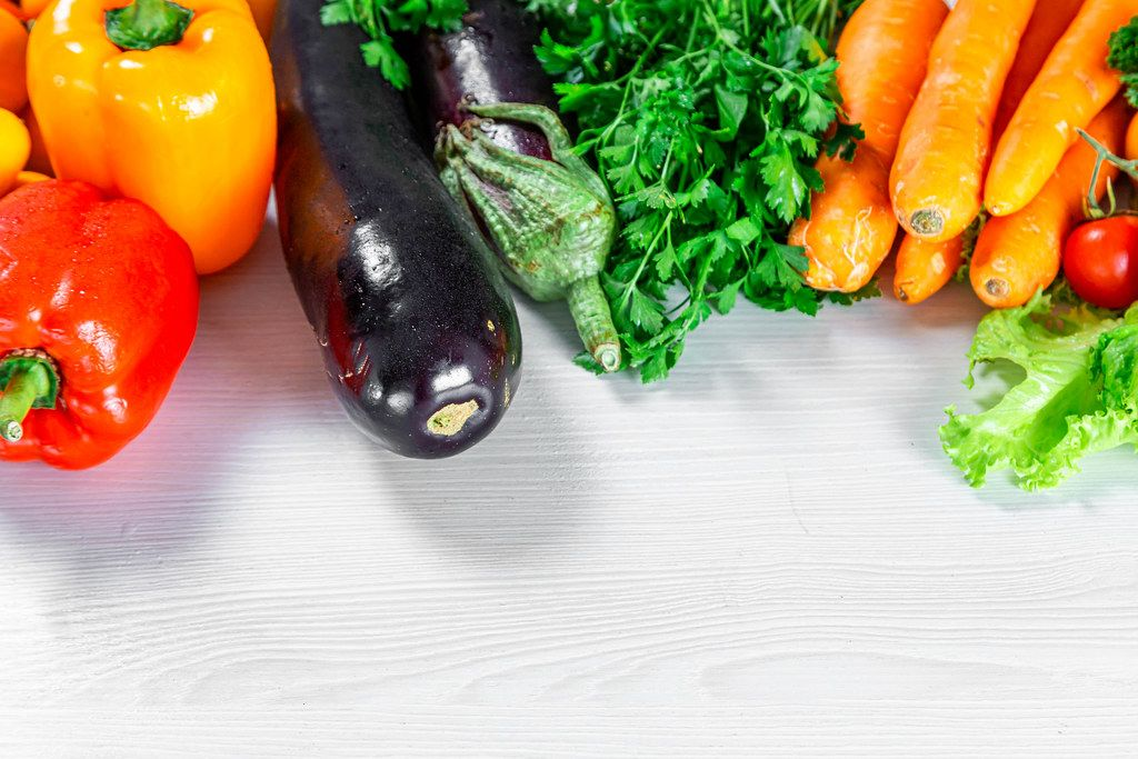 Pepper, eggplant, parsley and carrot on white wooden background