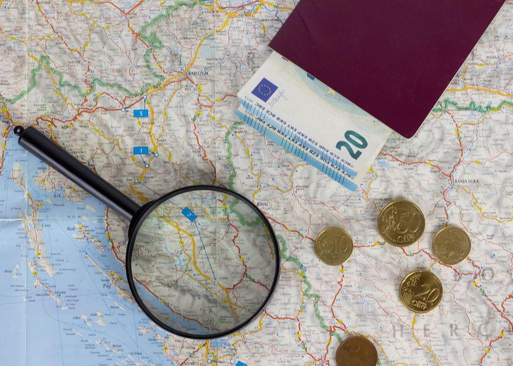 Perfektes Reiseziel aussuchen. Reisepass und Lupe auf einer Landkarte