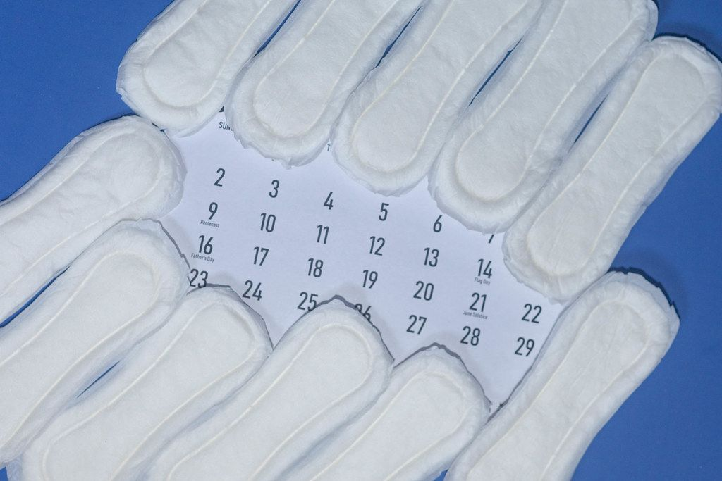 Period days concept. Sanitary napkins and calendar
