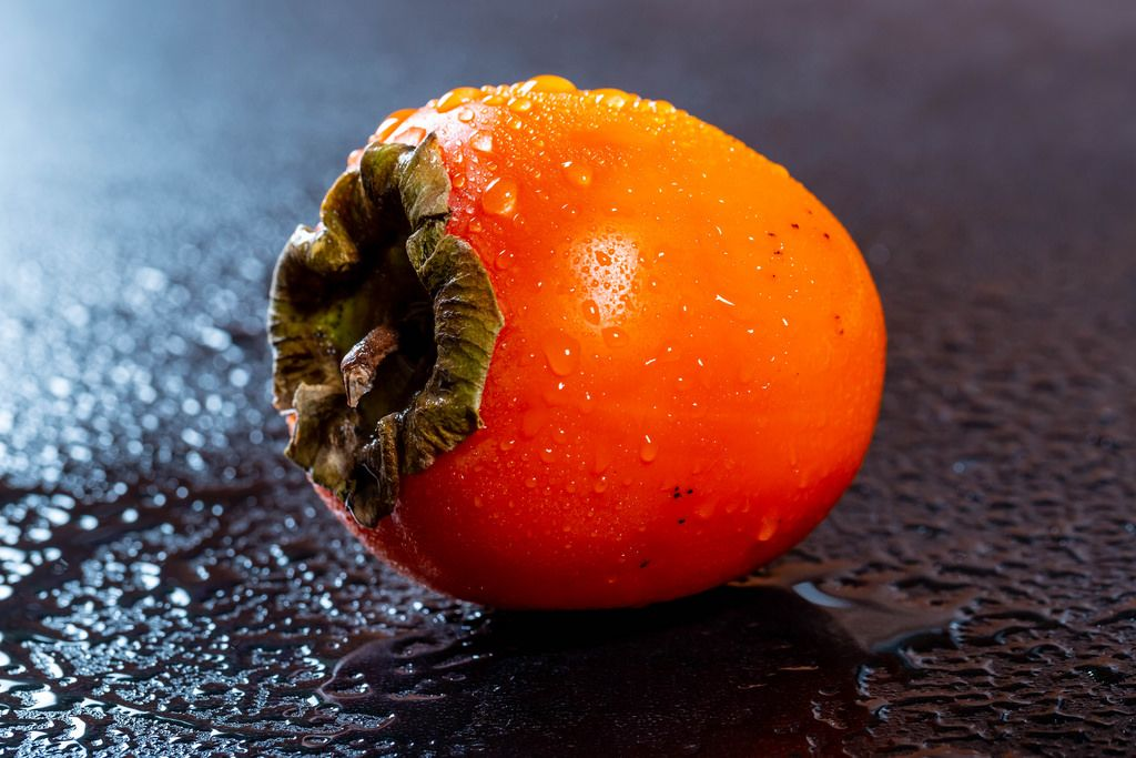 Persimmon fruit on dark background with water drops .