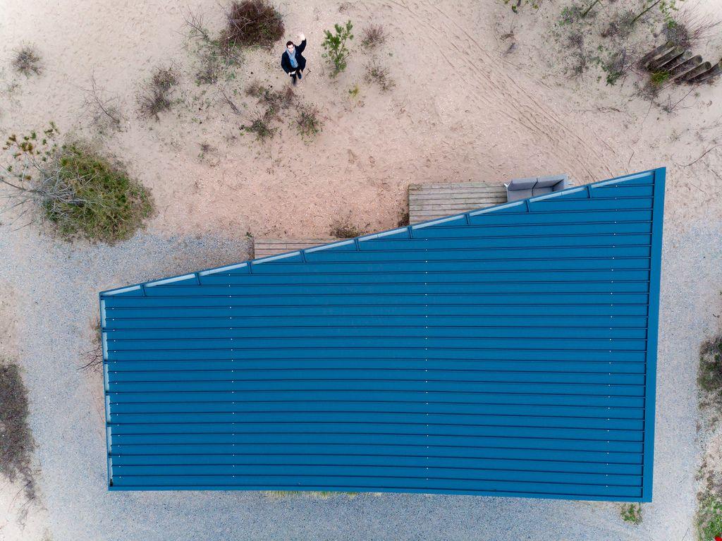 person neben haus mit asymmetrischem blauem dach winkt drohne zu marco verch bilder und fotos. Black Bedroom Furniture Sets. Home Design Ideas