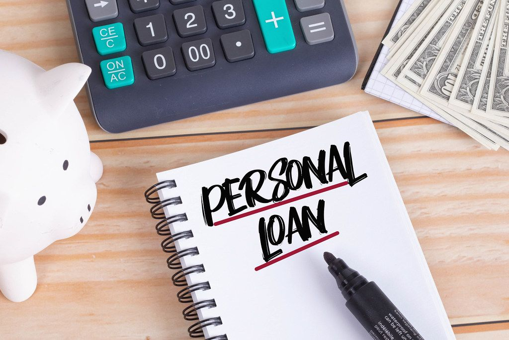 Personal loan text in notebook with piggy bank and calculator on wooden table