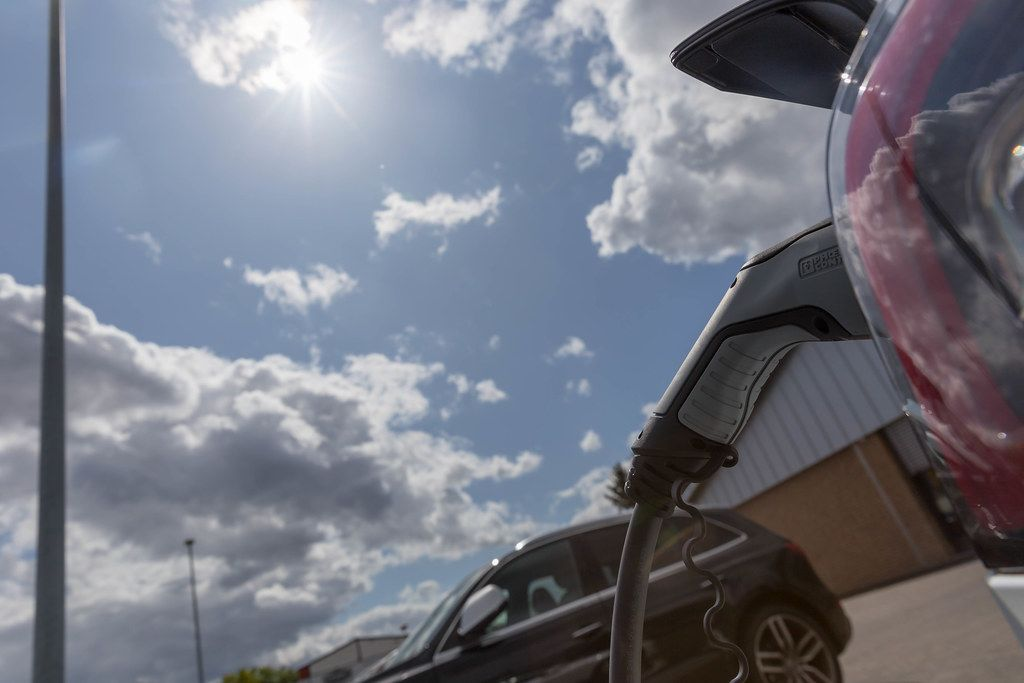 Phoenix Contact Type 2 plug is used to charge the Tesla Model 3 with sun energy at an Aldi-Süd parking lot, with clouds in front of the sun