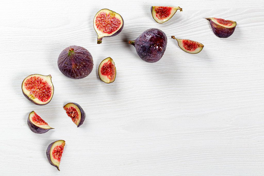 Pieces of fresh figs and whole fruit on a white wooden background with water drops