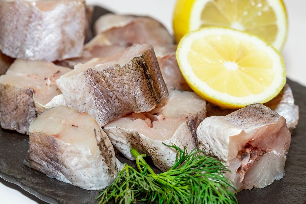 Pieces of raw fish hake with herbs and lemon