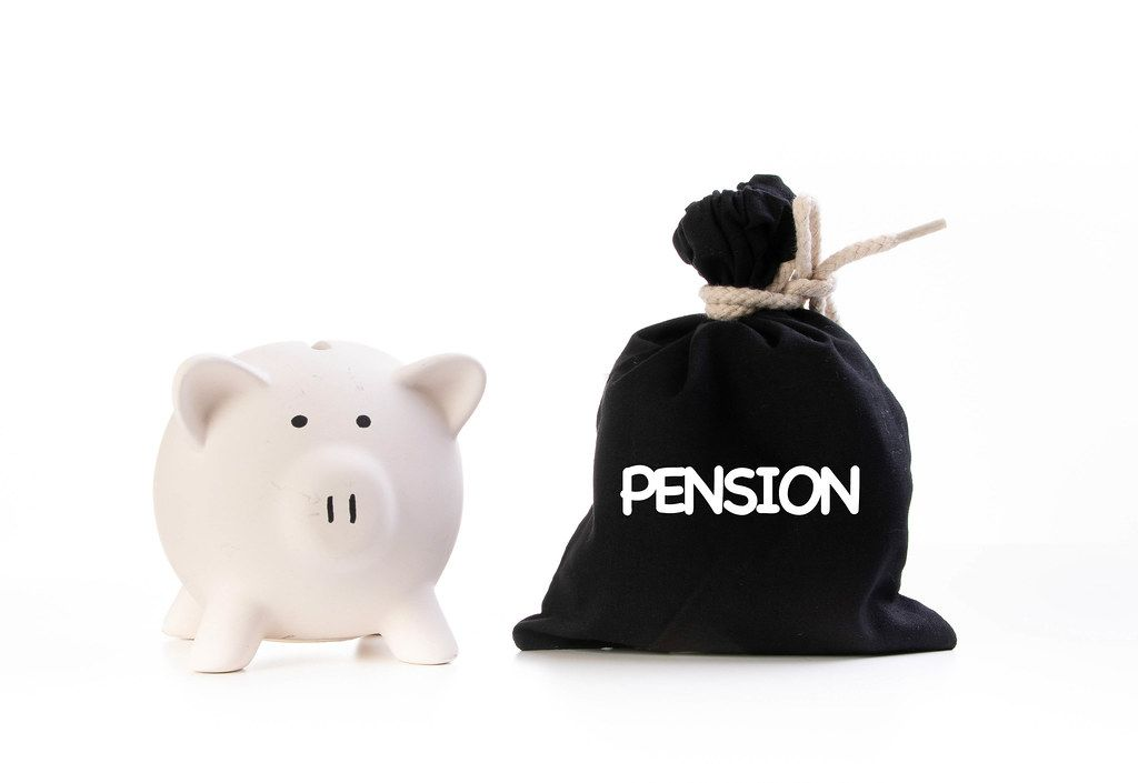 Piggy bank and money bag with Pension text on white background