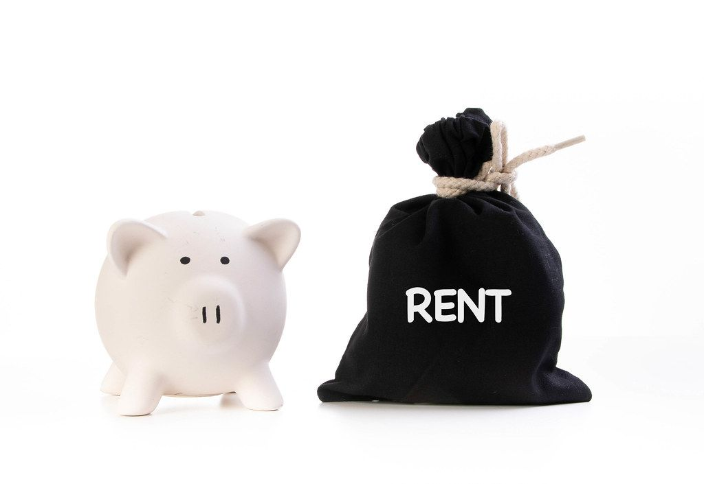 Piggy bank and money bag with Rent text on white background