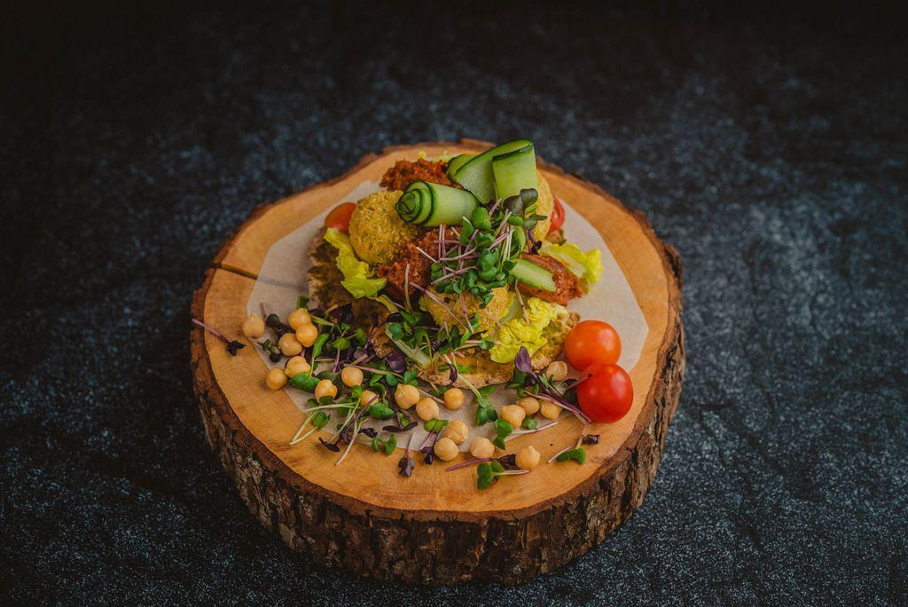 Pikante Hähnchen und Pesto-Bällchen mit allerlei farbenfroher Garnierung präsentiert auf Baumstammscheibe - frontale Nahansicht