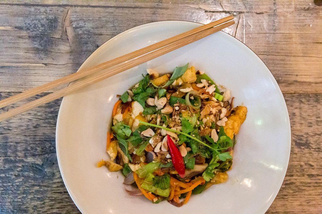 Pikantes veganes Gericht des Chum Chay vietnamesischen Restaurants in Köln: Bio-Tofu mit Zwiebeln, Pak-Choi, Champignons, Zuckererbsen und Erdnüssen in Limetten-Chili Sauce