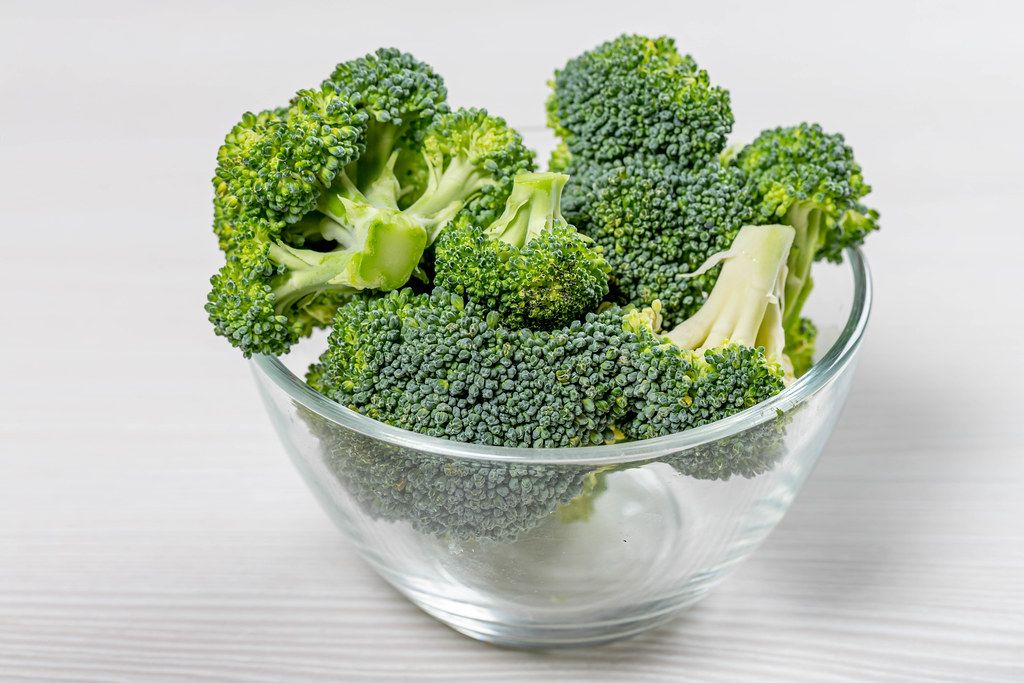 Pile broccoli in a glass bowl on a white background (Flip 2019)