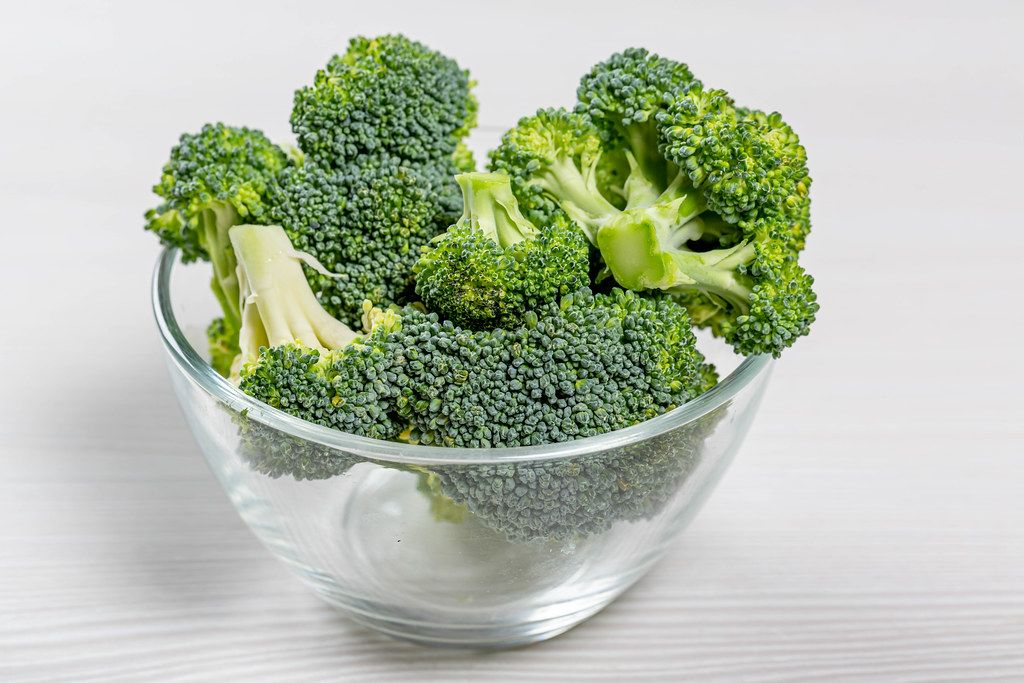Pile broccoli in a glass bowl on a white background