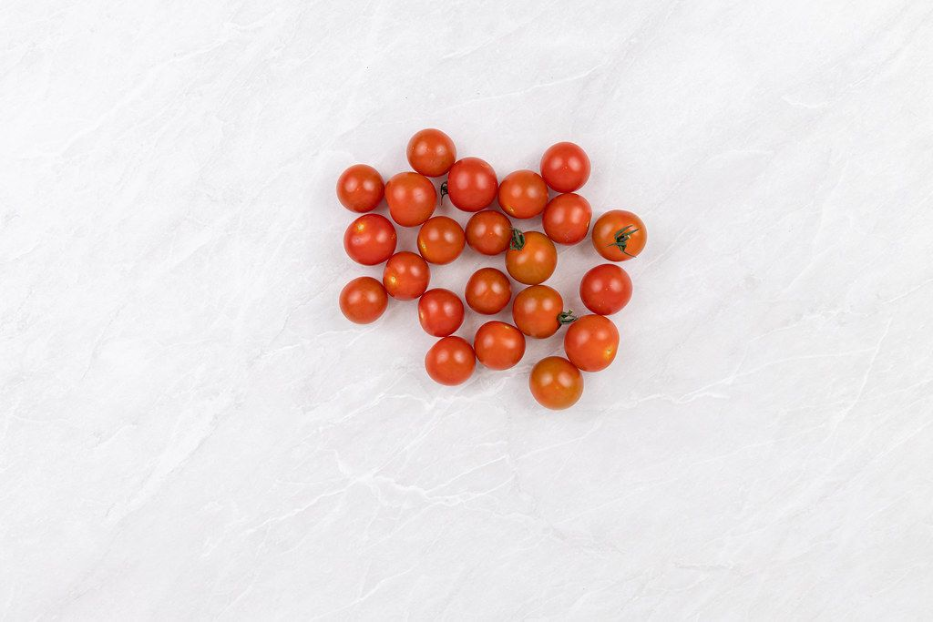 Pile of Cherry Tomatoes on the grey marble table with copy space
