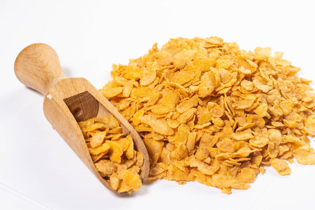 Pile of Corn Flakes with wooden measuring Spoon