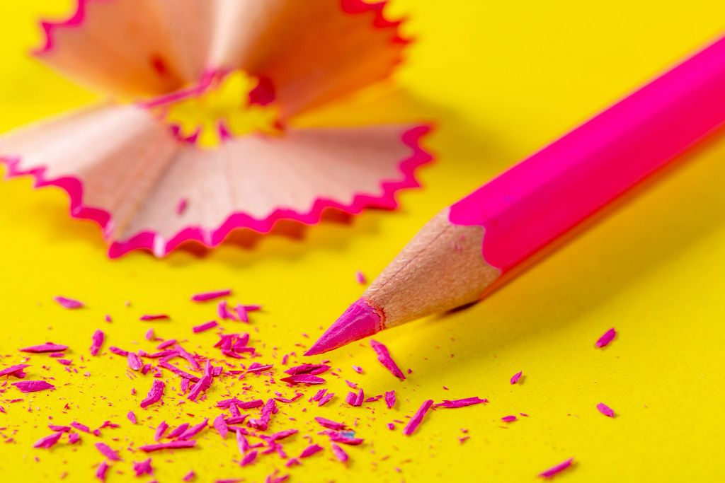 Pink pencil and shavings on yellow paper background