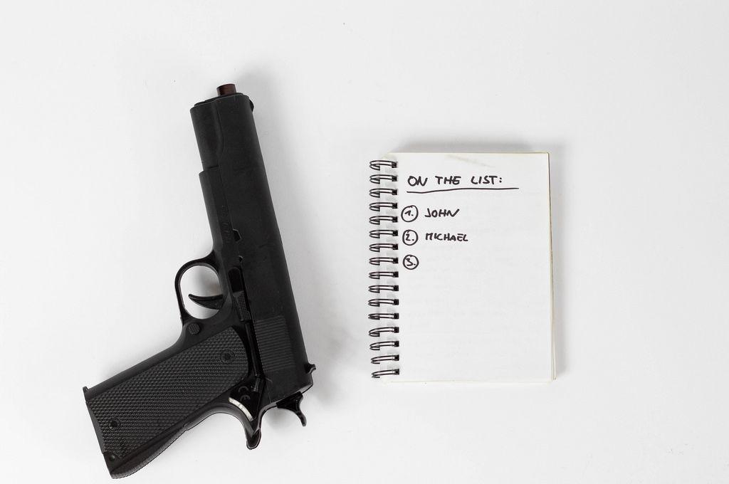 Pistole und eine schwarze Liste mit Namen. Rachegelüste