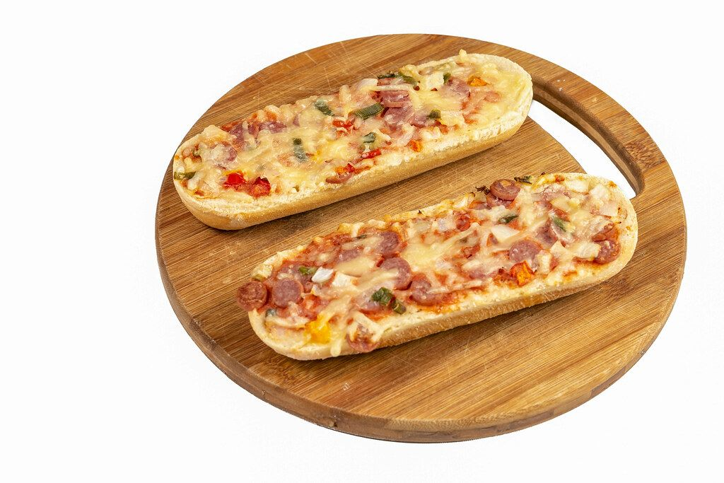 Pizza Baguette on the round wooden board
