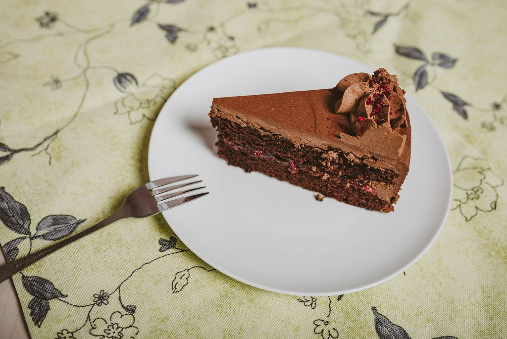 Plate with slice of tasty homemade chocolate cake_top view (Flip 2019)