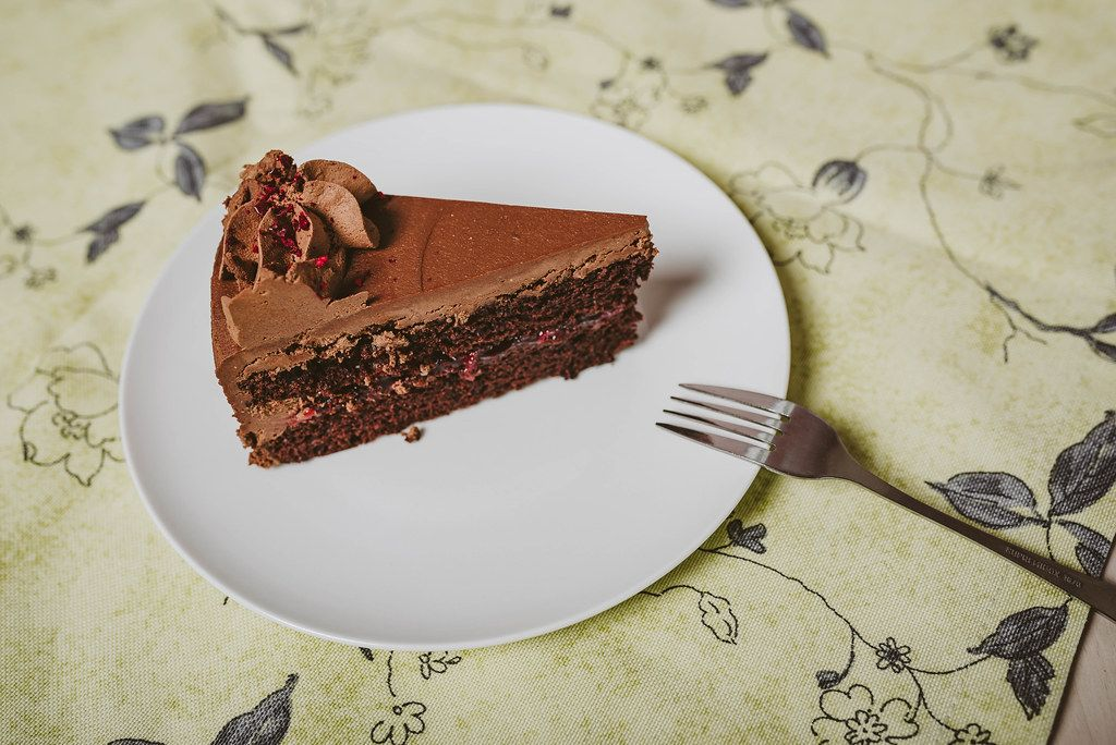 Plate with slice of tasty homemade chocolate cake_top view