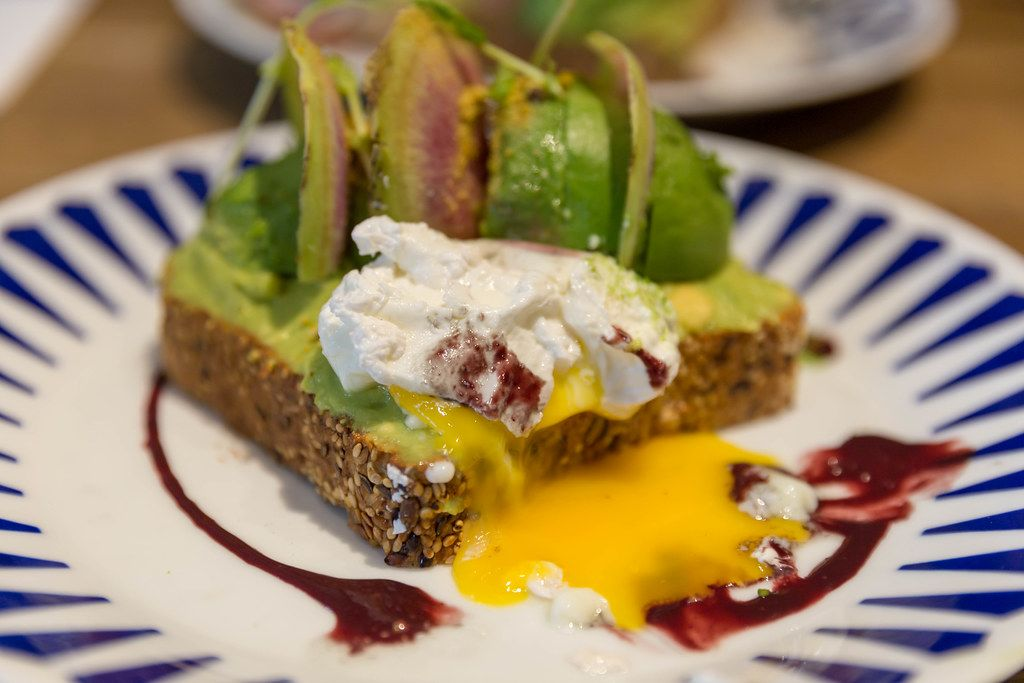Poacched egg topping on avocado toast with açai and yuzu sauces at Flax&Kale restaurant in Barcelona