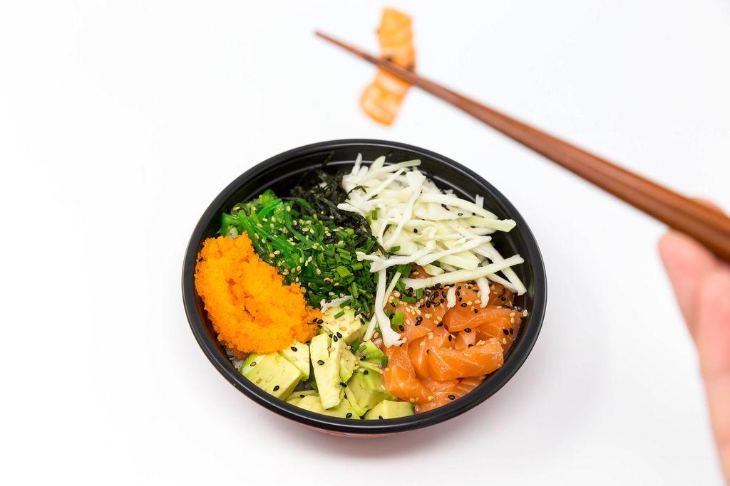 Poke Bowl Lachs Teriyaki - mit Sushireis, Lachs, Avocado, Krautsalat, Wakame Salat, Wasago, Nori, Teriyaki-Sauce, Soja-Sauce, Sesam und Schnittlauch - Ein Stück Lachs wird mit den Essstäbchen genommen