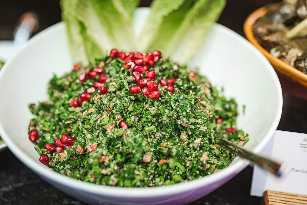 Pomegranate Salad with Mint Fresh Leaves in Glass Bowl