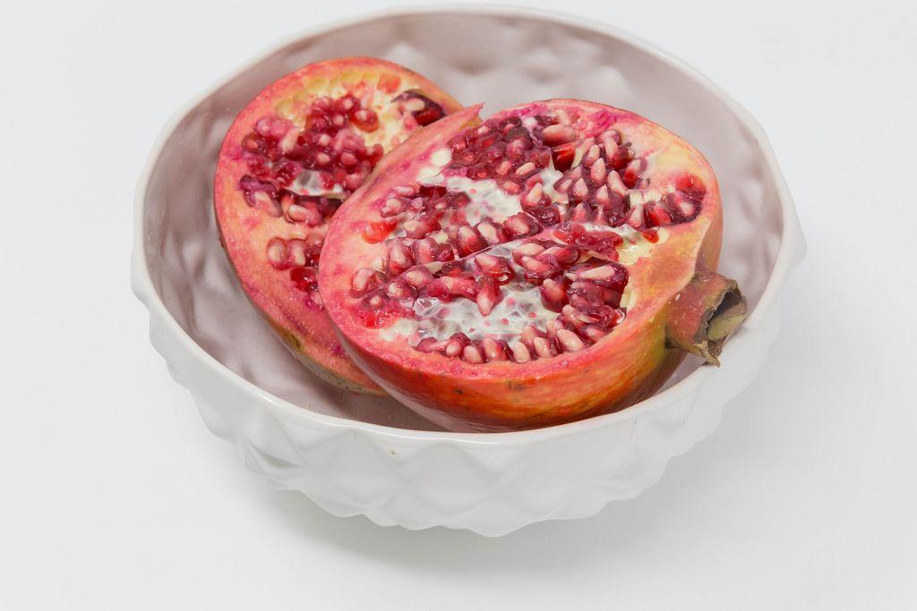 Pommegranate halfs in white bowl on white background