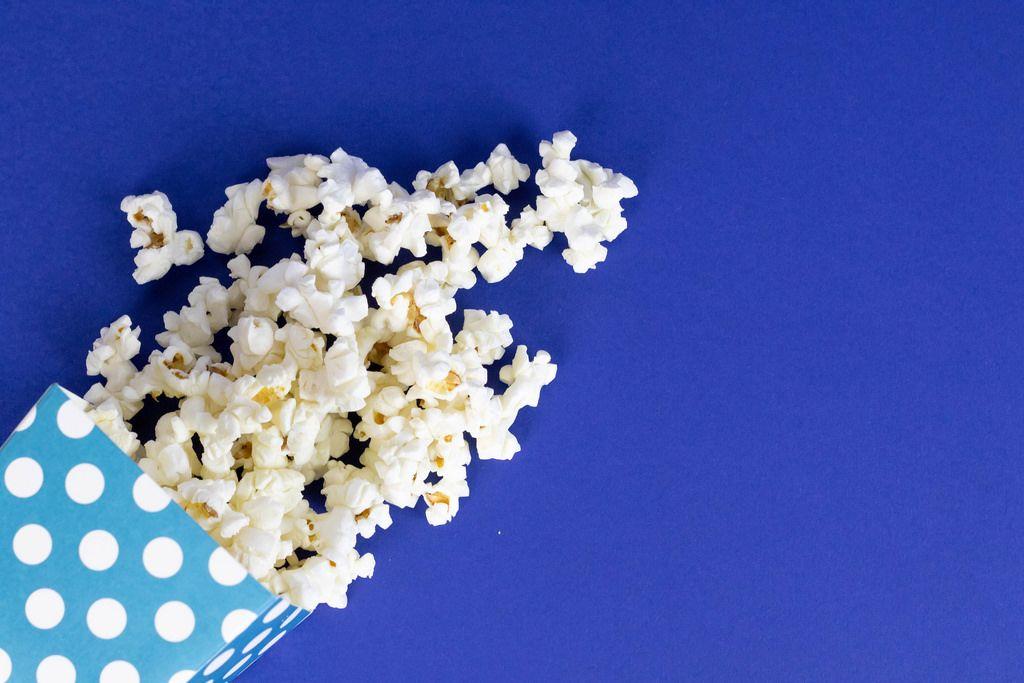 Popcorn in Papiertüte vor blauem Hintergrund