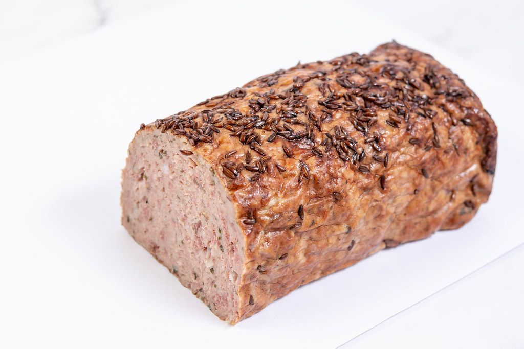 Pork and Chicken Meat Loaf with Cumin above white background