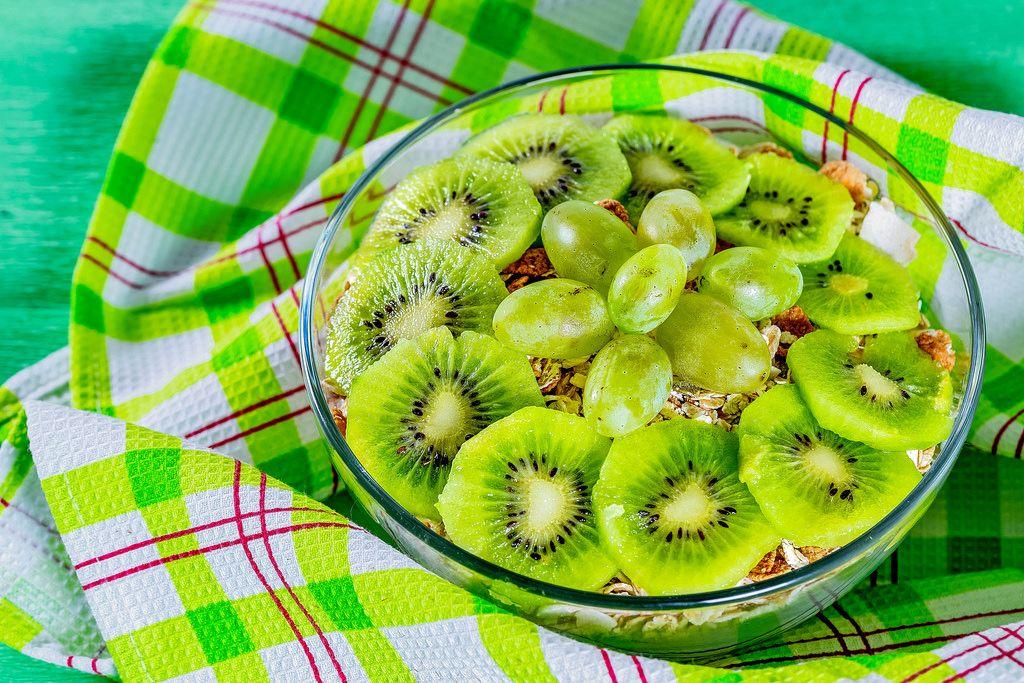 Porridge with flakes with slices of fresh kiwi on a green background