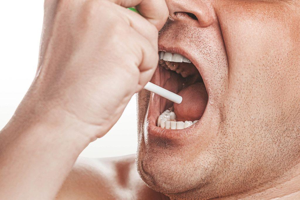 Portrait of a sick man sprays therapeutic aerosol in the oral cavity