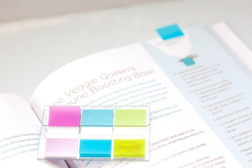 Post-It-Notizzettel in verschiedenen Farben, ein blauer am oberen Rand einer Seite