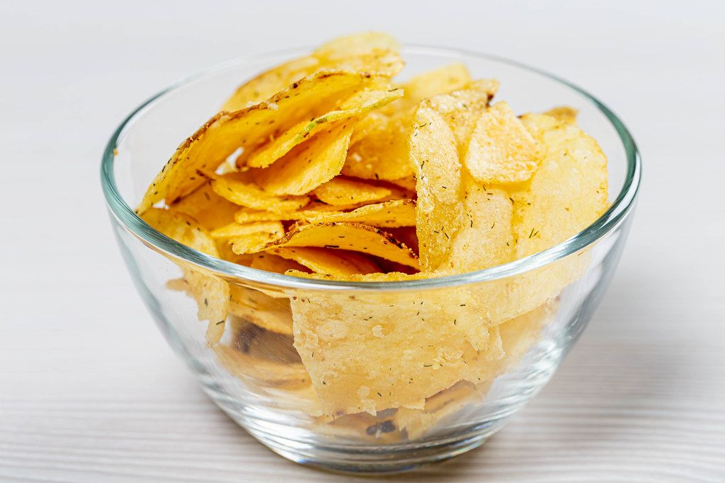 Potato chips in a glass bowl on a white table (Flip 2019)