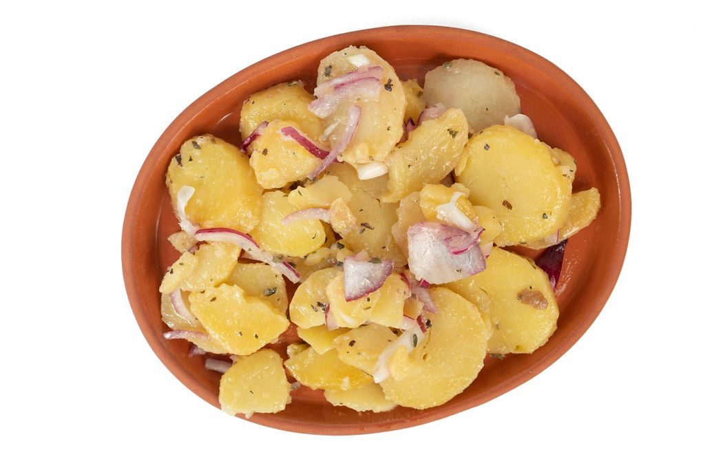Potatoe Salad with sliced Onions above white background