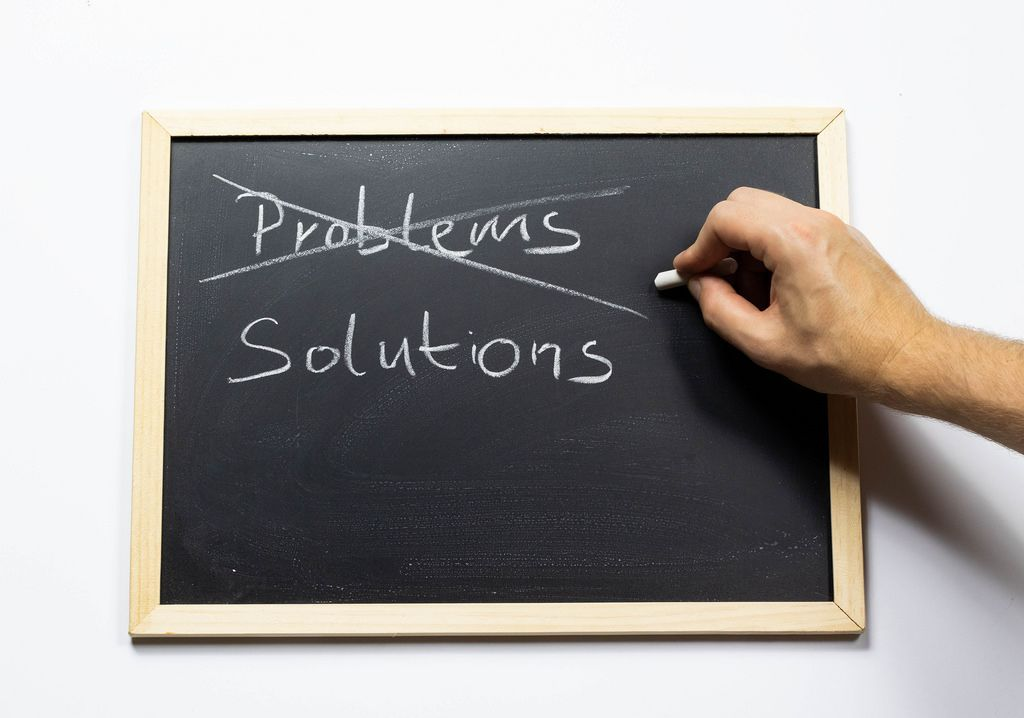 Probleme durchstreichen und Lösungen auf einer Kreidetafel aufschreiben