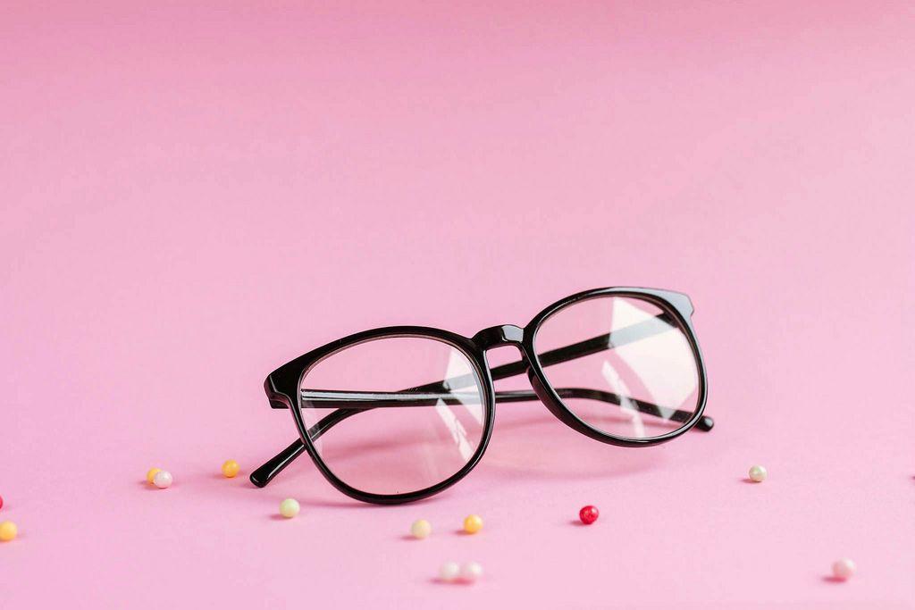 Produktfoto einer Brille vor rosafarbenem Hintergrund