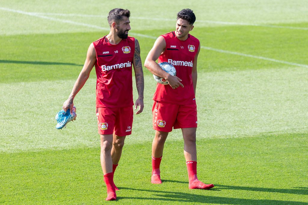 Professional football player Kerem Demirbay and Nadiem Amiri walking barefoot, without shoes, after the football team practice session