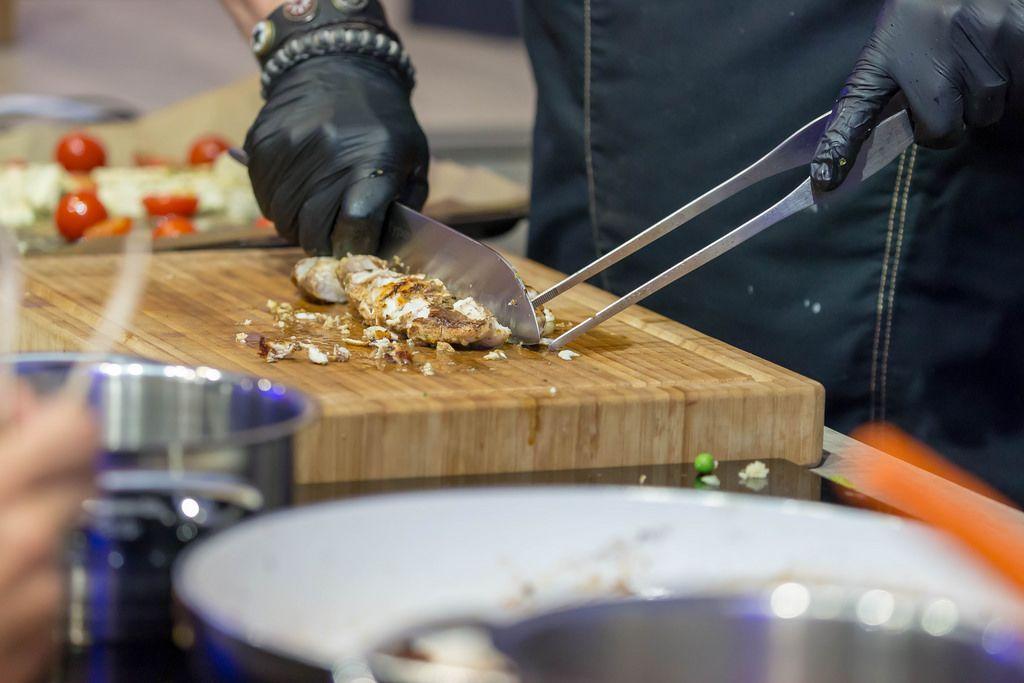 Profi-Koch zerkleinert gegrilltes Fleisch auf einem Küchenbrett