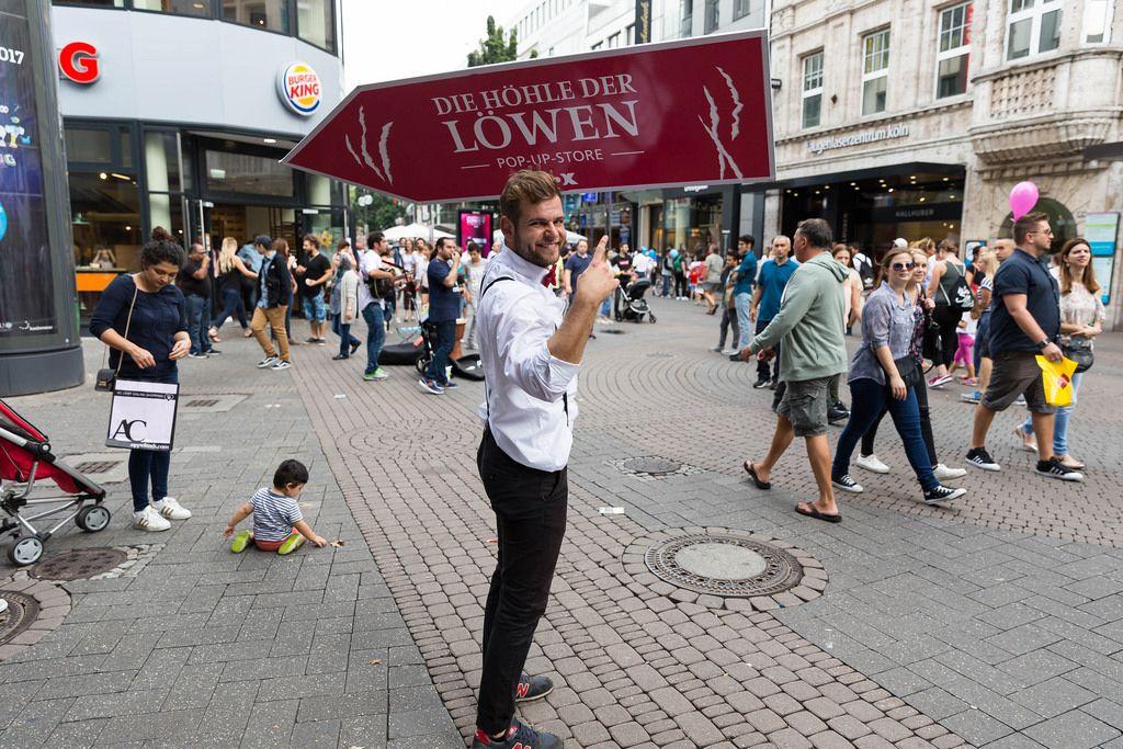 Promoter mit dem Transparent für das Pop-up-Store Die Höhle des Löwen